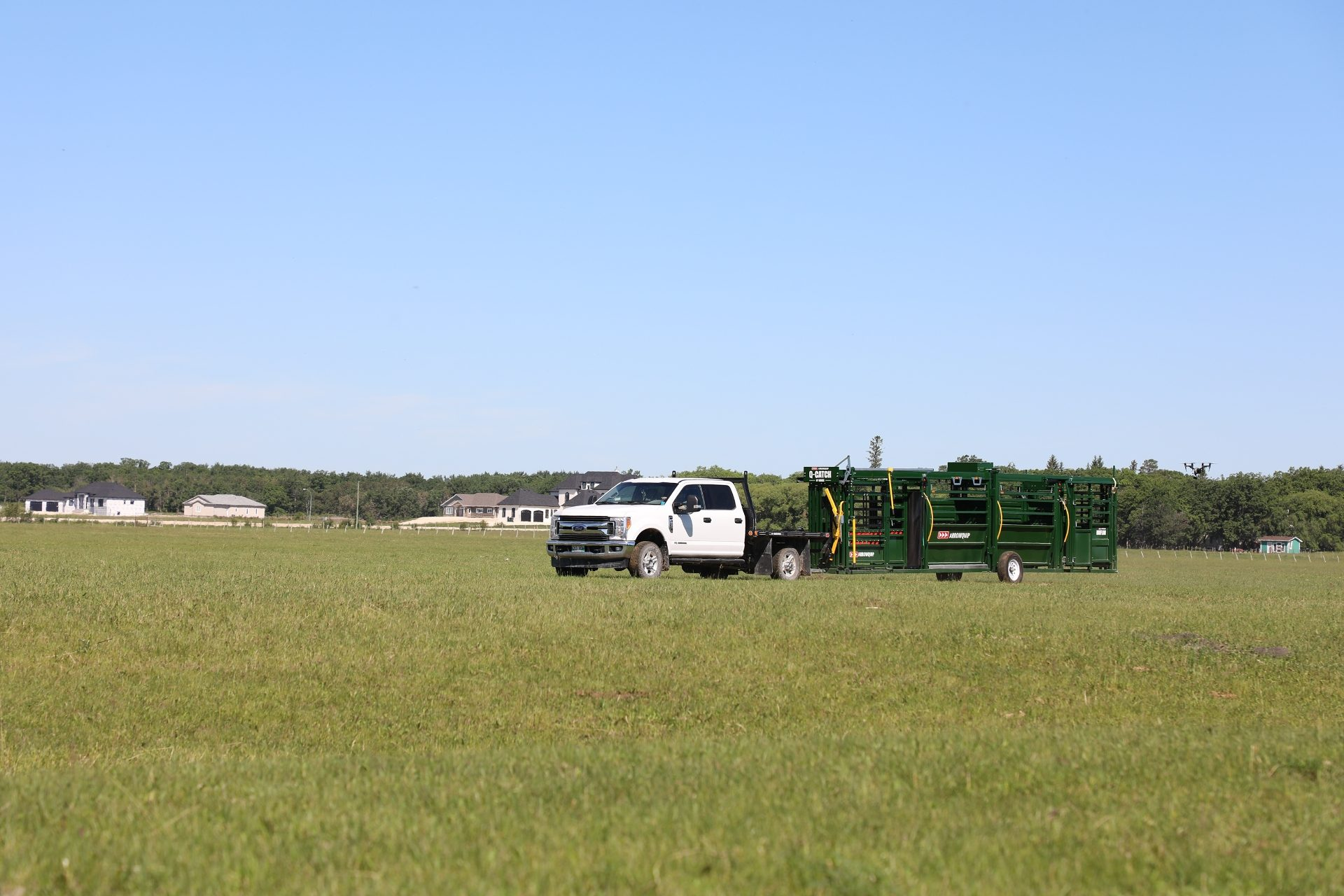 Q-Catch 87 Series Portable Cattle Handling System with 18' Alley being towed across grass field