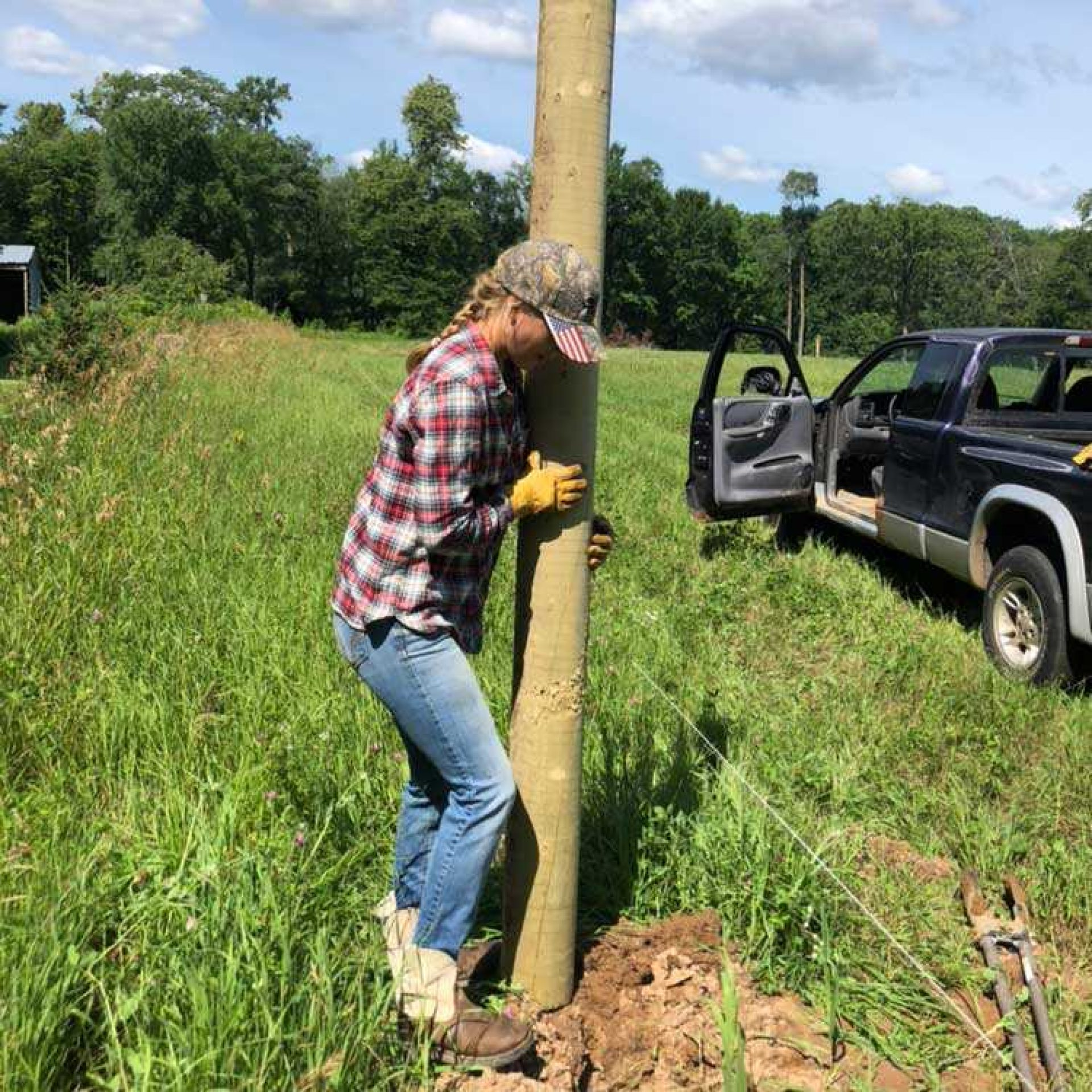 Young woman installing fence posts