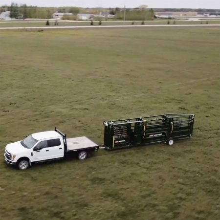 Towing a portable cattle handling system through a field.