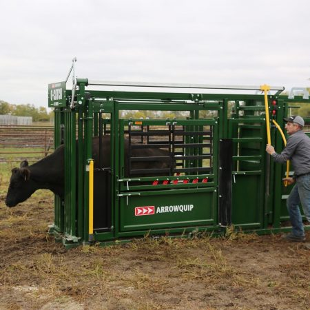 Rancher working on a squeeze chute for cattle