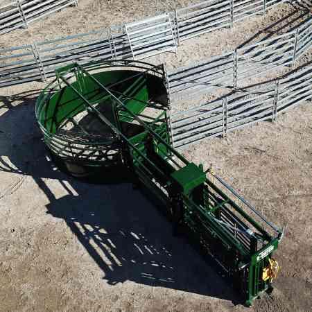 Vue de haut du système combiné mobile de cage de contention, couloir de contention et enclos pivotant Q-Catch installé au sol dans le système